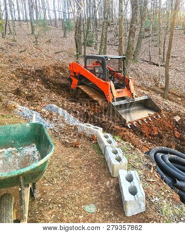 A Red Bucket Loader On A Hill At A Job Site, Working To Build A Retaining Wall For Drainage.
