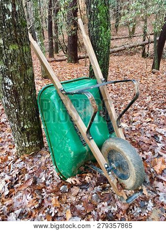 A Green Wheelbarrow In The Woods Propped Against A Tree, Surrounded By Leaves, Concept For Fall Yard