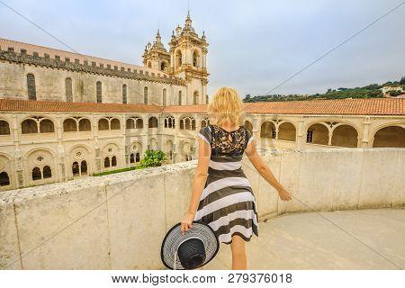 Blonde Caucasian Tourist Woman Looking At Mosteiro De Santa Maria De Alcobaca. Tourism And Travel In
