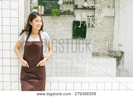 Portrait Of A Happy Young Asian Barista In Apron Smiling And Looking Away In Front Of Her Small Coff