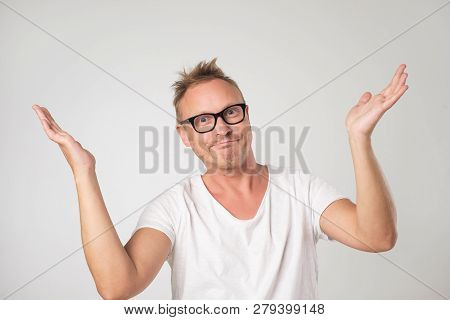 Mature Man In White Shirt Shrugging Shoulders Who Cares So What.
