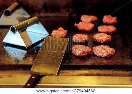 Cooking Burgers In The Restaurant On The Grill. The Kitchen Of Fast Food Restaurant