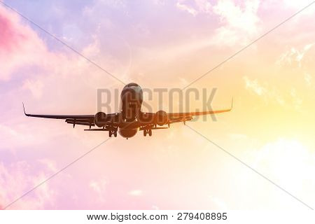 Airplane Silhouette In Warm In The Yellow-pink Tones Of The Sky And Clouds. Copcept Travel To Warmer