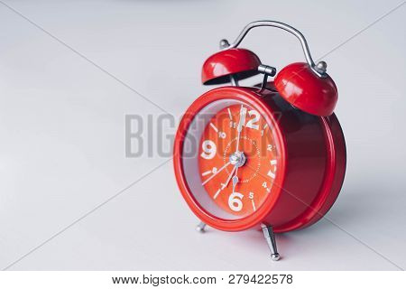 Red Alarm Clock On White Table.time Management And Punctuality At Work Concept.