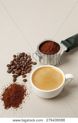 Cup Of Black Coffee Next To Coffee Beans And Grains, Handle Coffee Machine Filter On Gray Background