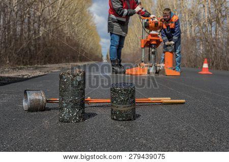 Worker Cut By The Core Sampler Samples Of Asphalt Concrete On The Road. Asphalt Concrete Cores Close