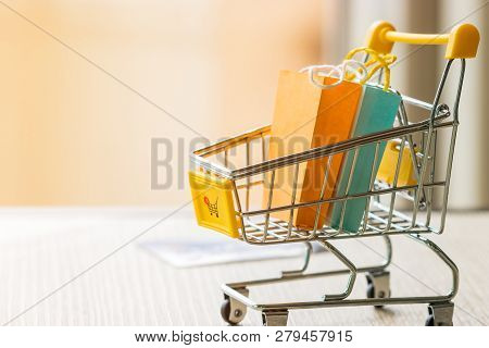 Paper Shopping Bags In Trolley With Add To Cart Symbol On Wood Table. Consumer Can Buy Products Dire
