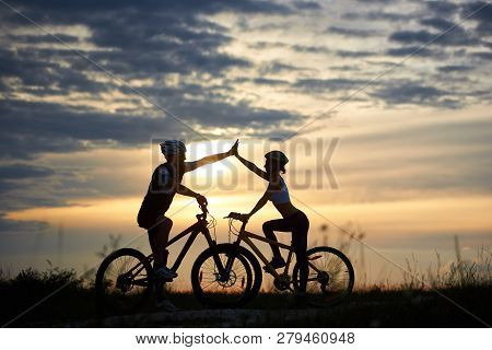Adorable Couple In Helmets Taking Family Ride On Bicycles, Standing And Posing. Silhouettes Of Sport