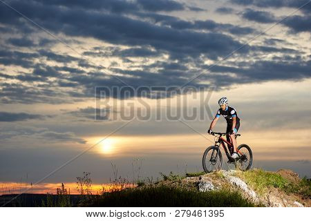 Professional Cyclist Riding Mountain Bike On Rock Hill With Enthusiasm. Energetic And Athletic Man I