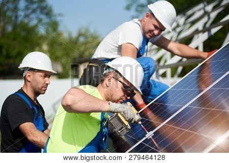 Three Professional Technicians Installing Solar Photo Voltaic Panel To Metal Platform On Blue Sky Ba