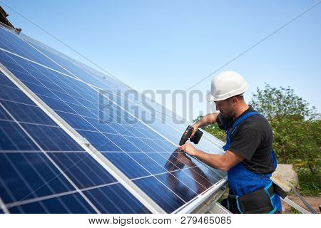 Technician Connecting Solar Panel To Metal Platform Using Electrical Screwdriver On Blue Sky Copy Sp