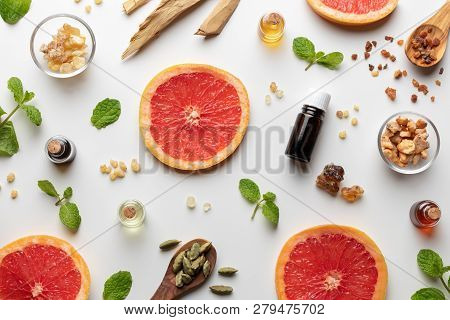 Bottles Of Essential Oil With Fresh Grapefruit, Peppermint, Myrrh, White Sandalwood And Other Ingred