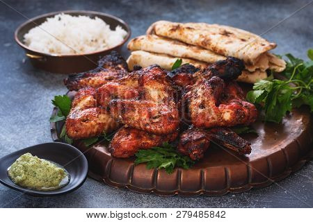 Indian Tandoori Chicken Wings Served With Pilau Rice And Garlic Naan , Selective Focus