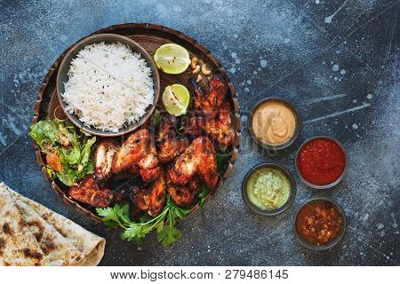 Tandoori Chicken Wings Served With Pilau Rice,  Soft Garlic Cheese Naan With Different Chutney Dippi