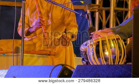 Two Men Playing Traditional Indian Tabla Drums And Flute On Stage Of Ethnic Open Air Concert. Relaxa