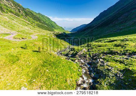 Balea Stream Of Fagaras Mountains. Wonderful Serpentine Of Transfagarasan Road On The Left Side. Bea