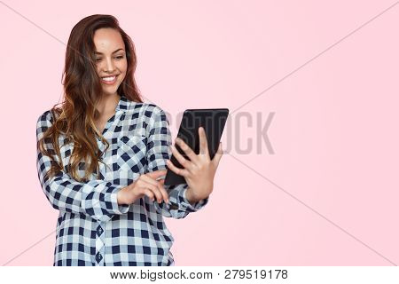 Young Charming Teenage Using Touchpad And Taking Selfie With Smile On Pink Backdrop