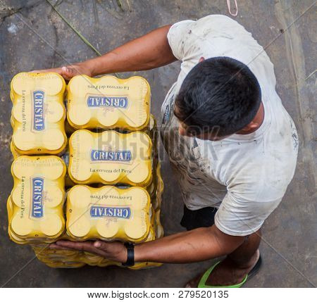 Loreto, Peru - July 15, 2015: Man Holds A Stack Of Beer Cans Of A Peruvian Brand Cristal