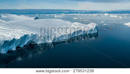 Climate Change and Global Warming - Giant Iceberg from melting glacier in Ilulissat, Greenland. Aerial drone of arctic nature landscape famous for being heavily affected by global warming. Boat.