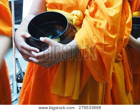 Monk Wear Yellow Robe Holding Black Alms Bowl For Food Offering In Morning.