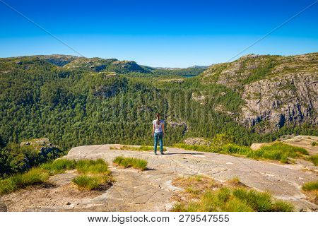 Hiker Standing On Preikestolen And Looking On The Mountain Next To Preikestolen - Famous Cliff In No