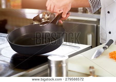 Chef Greasing Pan With Oil. Cooker Man Pouring Oil On Pan From Metal Sauce Boat. Preparation For Fry