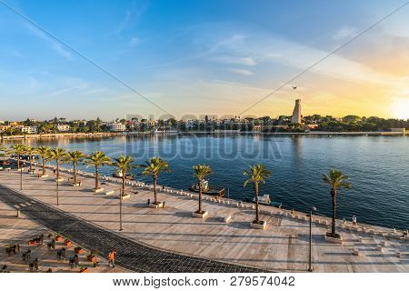 Brindisi, Italy - September 20 2018: The Italian Sailor Monument, Promenade And Bay As The Sun Sets