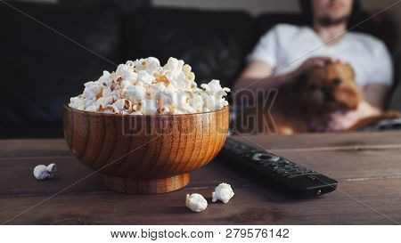 Wooden Bowl With Salted Popcorn And Tv Remote On Wooden Table. In The Background, A Man With A Red D
