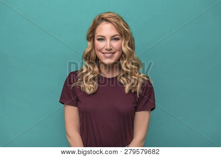 Portrait Of Smiling Woman On Blue Background.
