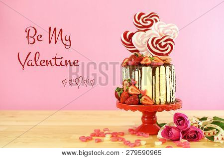 Valentines Day Candyland Drip Cake Decorated With Heart Shaped Lollipops.