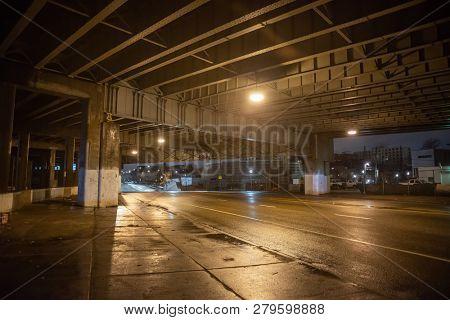 Gritty dark city highway bridge and street underpass at night in Chicago