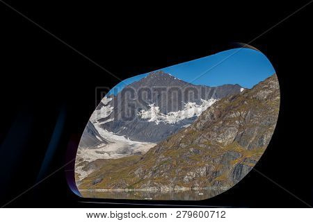 Scenic View Through Ship Port Hole/window Of Snow Covered Mountains In The Glacier Bay National Park