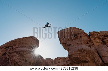 Challenge, Risk And Freedom Concept. Silhouette A Man Jumping Over Precipice Crossing Cliff