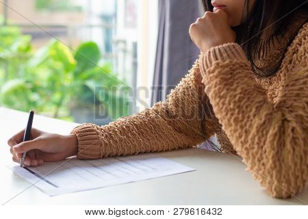 Close-up Of Pensive Lady Filling Tax Form. Busy Woman In Sweater Sitting At Table And Working With P