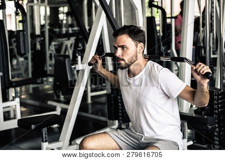Handsome Man Is Rowing Exercise With Bodybuilder Machine In Fitness Club.,portrait Of Strong Man Doi