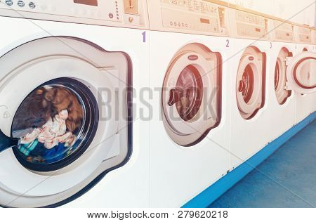 Row Of Industrial Laundry Machines In Commercial Laundromat. Concept Business Washer Shop.