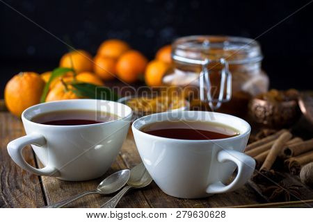 Tea with cinnamon and tangarine marmalade.  Clear glass and white dish. Dark food photo style. Christmas winter or autumn mood. Homemade citrus cinnamon and anise stars marmalade. Winter family tea poster
