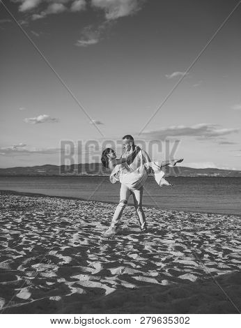 Man Carries Woman In White Dress, Couple Happy On Vacation. Couple In Love Stand On Beach, Seashore.