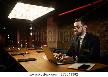 Serious director of classy restaurant working in the net while sitting by table in front of laptop