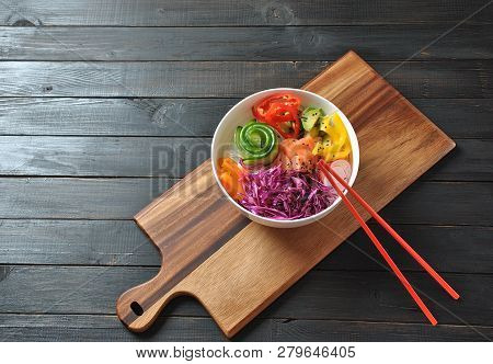 Poke bowl with fresh salmon, crystal noodles, radish, avocado, sweet pepper, cucumber, sesame seeds, red cabbage. Organic food. Fresh seafood recipe. Food concept poke bowl on wooden background poster