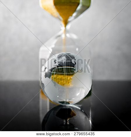 Reflection Of Gold Sand Running Through The Shape Of Hourglass With World Globe Crystal Glass On Tab