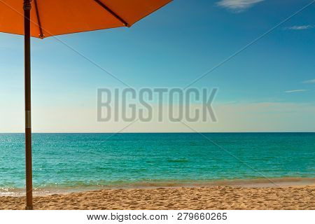 Orange Beach Umbrella On Golden Sand Beach By The Sea With Emerald Green Sea Water And Blue Sky And