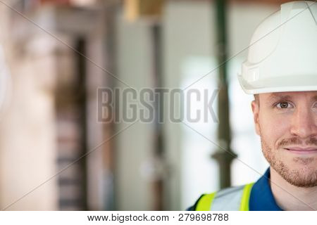 Cropped Portrait Of Male Construction Worker On Building Site Wearing Hard Hat