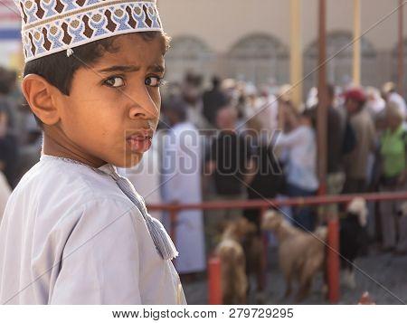 Nizwa, Oman - November 2, 2018: Portrait Of Child Turning Around Surprised By The Camera At The Frid