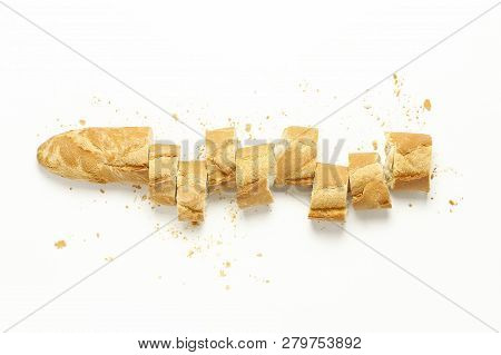 Top View Of Sliced Baguette With Crumbs On White