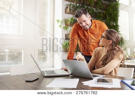 Group Of Business People Working Together On Laptop In The Office