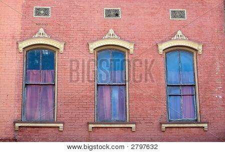 Three Windows And Pink Brick