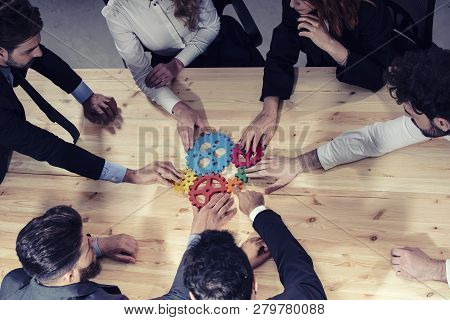 Business Team Connect Pieces Of Gears. Photo From Above. Teamwork, Partnership And Integration Conce