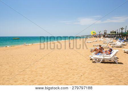 Side, Turkey - June 6, 2018: People on the beach on Turkish Riviera near Side. Turkish Riviera is a popular tourist destination on the southwest Turkey area.