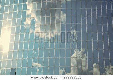 Clouds Reflected On Glass Facade Wall Of Building. Cloudy Blue Sky Reflection In Windows. Modern Gla